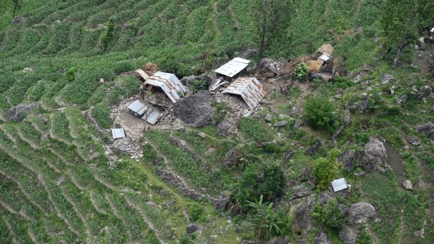 This aerial view from an Indian Army helicopter shows a cluster of damaged homes in the hills of Gorkha some 60kms north-west of Kathmandu on April 28, 2015.  Hungry and desperate Nepalese villagers rushed towards a relief helicopter begging to be airlifted to safety after a huge earthquake that has killed at least 4,349 people devastated their remote community.    AFP PHOTO / SAJJAD HUSSAIN