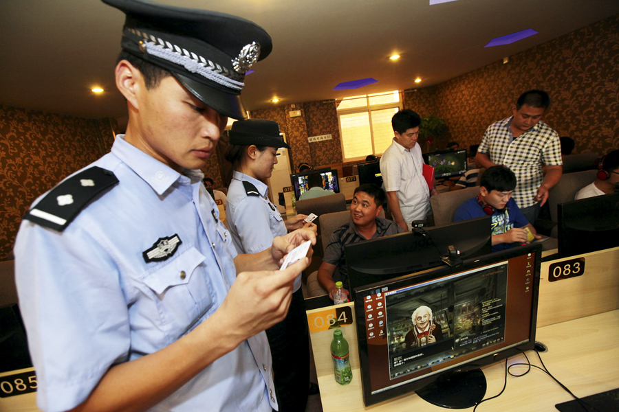 --FILE--Chinese police and law enforcement officers check ID cards of young netizens playing online games or watching online videos at an Internet cafe in Zaozhuang city, east Chinas Shandong province, 31 July 2013. Chinese Internet users are now required to register their real names to upload videos to Chinese online video sites, an official body said, as the Communist Party tightens its control of the Internet and media to suppress anti-government sentiment. The new rule has been implemented to prevent vulgar content, base art forms, exaggerated violence and sexual content in Internet video having a negative effect on society, Chinas State Administration of Press, Publication, Radio, Film and Television (SARFT) said on its website. The rule is aimed at online dramas, micro-films and other online audio-visual programmes, the statement on the website said. It gave no further explanation.