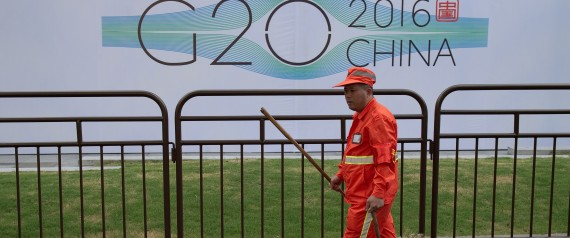 A cleaning worker walks around a hotel and signage for the G20 summit in Hangzhou on September 2, 2016. Factories have been closed to ensure blue skies, potential troublemakers detained and a quarter of the residents have left: welcome to Hangzhou, a city China's ruling Communist Party is determined will look its best for the G20 summit. / AFP PHOTO / NICOLAS ASFOURI / TO GO WITH AFP STORY: China-G20-diplomacy , Focus by Tom HANCOCK