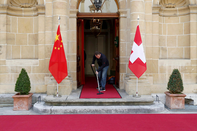 A staff member cleans the red carpet prior to the visit of Wang Yi, Foreign Minister of China (not pictured), and Didier Burkhalter, Foreign Minister of Switzerland (not pictured), in Neuchatel, Switzerland, on Monday, December 12, 2016. (KEYSTONE/Peter Klaunzer)